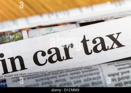 Newspapers stacked up with headline about car taxes in the center of the image. Shallow depth of field. - Stock Photo