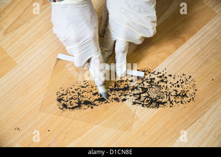 Police crime scene unit. Securing of evidences. saving a footprint, shoe print with a foil. - Stock Photo