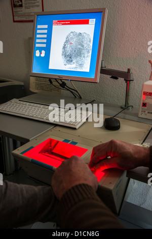 Police, taking fingerprints with a digital laser scanner. - Stock Photo