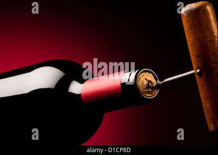 Old Corkscrew Opening a Bottle of Wine. - Stock Photo