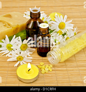 Oil in two different bottles, two homemade soap, bath salt, two candles with flames and chamomile flowers on a bamboo - Stock Photo