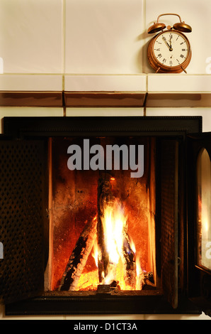 fireplace, flame and old-fashioned copper alarm clock on the mantelshelf - Stock Photo