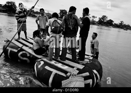 A makeshift inner tube raft, carrying immigrants from Central America, leaves the shore of the river in Tecún Umán, - Stock Photo