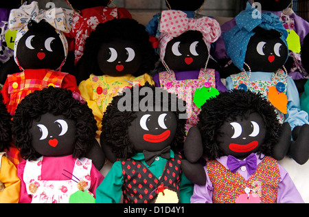Group of smiling golliwogs with bright and colourful clothing - hand-made toys - Stock Photo