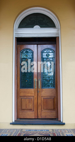 Ornate double timber doors with colourful stained glass panels and curved stained glass segment above door in cream - Stock Photo