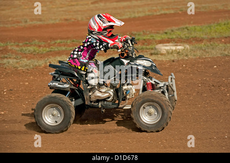 Young child - aged four - on quad bike wearing protective clothing and riding on dirt track - Stock Photo