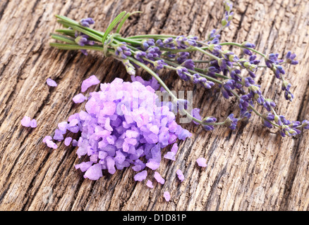 Bunch of lavender, and sea salt on a wooden table. - Stock Photo