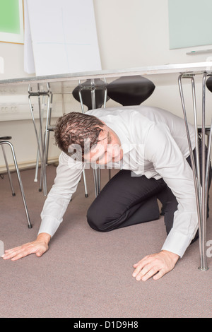 Man in white shirt sitting under table in an office searching for something that is lost. - Stock Photo