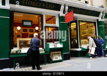 People browsing in the windows of book shops in Cecil Court in Central London. - Stock Photo