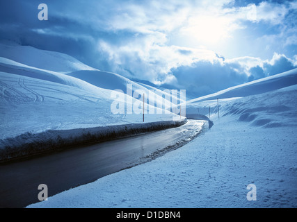 Picture of beautiful snowy highway, black clean asphalt road in mountains covered white snow, wintertime weather, - Stock Photo