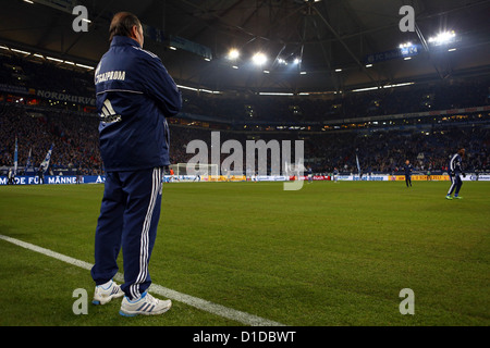 Schalke's head coach Huub Stevens stands on the sideline as he observes his players on the pitch during warm-up - Stock Photo