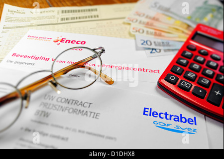 Calculator and Flemish invoices of Eneco and Electrabel, Belgian energy corporations, suppliers of electricity and - Stock Photo