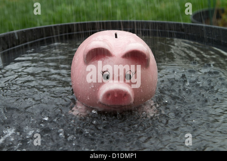 Pink Piggy bank getting wet in the rain - Stock Photo