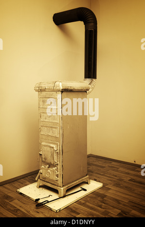 Old stove in the corner of the room - Stock Photo