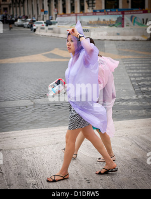 Asian tourists in plastic ponchos, Rome - Stock Photo