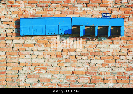 Background - aged red brick construction wall with old post boxes. - Stock Photo