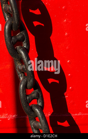 Black anchor chain on red steel ship, Helsinki, Finland - Stock Photo