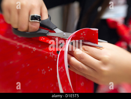 A woman wraps a christmas gift at a shop in Osnabrueck, Germany ...