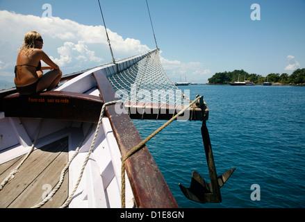 Tourist on a schooner cruising between the different beaches and islands around Parati, Rio de Janeiro State, Brazil - Stock Photo