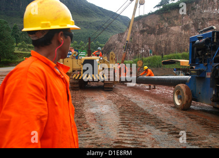 Workers putting pipes for natural gas near Congonhas, Minas Gerais, Brazil, South America - Stock Photo