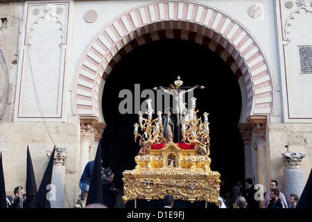 Jesus Christ on the Cross with Virgin Mary and Mary Magdalene on a gilded platform in procession during Holy Week - Stock Photo