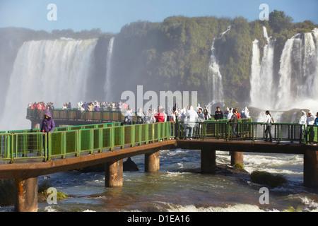Tourists on walkway at Iguacu Falls, Iguacu National Park, UNESCO World Heritage Site, Parana, Brazil, South America - Stock Photo