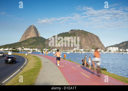 People exercising on pathway around Botafogo Bay with Sugar Loaf Mountain in the background, Rio de Janeiro, Brazil - Stock Photo