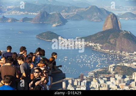 Tourists enjoying view of Sugar Loaf Mountain (Pao de Acucar) and Botafogo Bay from Corvocado, Rio de Janeiro, Brazil - Stock Photo