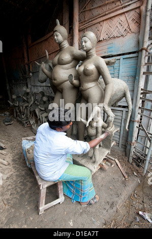 Sculptor working on moulded deity and Nandi the bull, Kumartuli district, Kolkata, West Bengal, India - Stock Photo