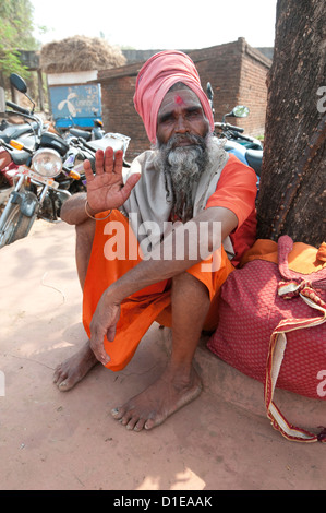 Travelling saddhu dressed in holy colour orange, resting beneath a village tree, Bhubaneshwar, Orissa, India, Asia - Stock Photo