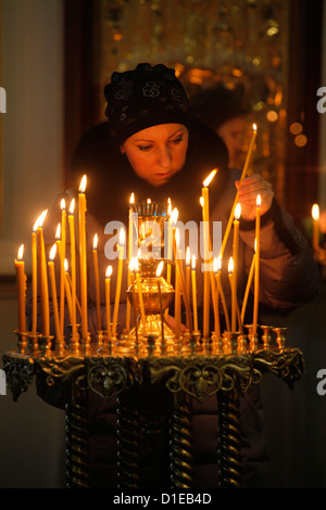 Woman lighting a candle, Trinity Cathedral, St. Petersburg, Russia, Europe - Stock Photo