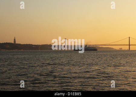 A cruise liner turns into the sunset, on the River Tagus under the 25 April Bridge and Christus Rei statue, Lisbon, - Stock Photo