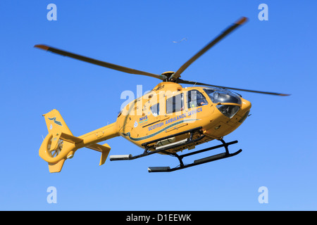 Yellow Scottish Air Ambulance Service Helicopter flying overhead with a casualty from a rescue mission. Sutherland - Stock Photo