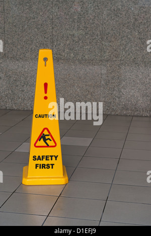 Caution wet floor sign on tiled floor with stone wall on background - Stock Photo