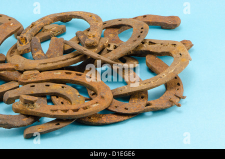 stack of old retro horse shoes on blue background - Stock Photo
