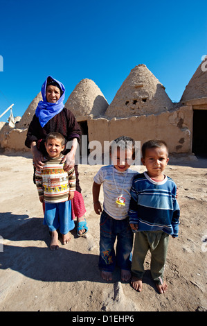 Arab children in front of the adobe brick 'beehive' tholos conical shaped house of Harman, Turkey - Stock Photo
