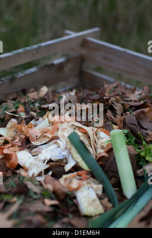 Compost heap in the garden with vegetable waste - Stock Photo