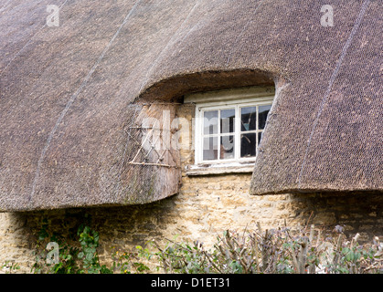 White painted wooden window under thatched roof of rural cottage - Stock Photo