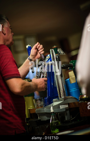A barman pulling a pint of cold lager on a Saturday night, in a working mens club, UK - Stock Photo