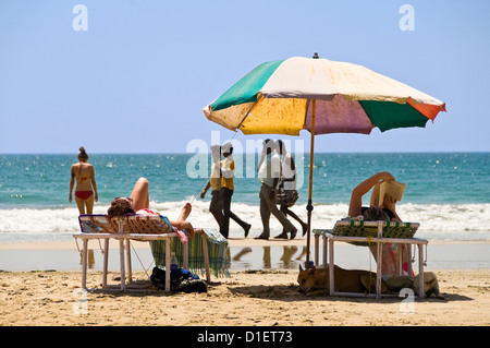 Horizontal view of Western female tourists sunbathing on the beach at Varkala with a group of Indian men walking - Stock Photo