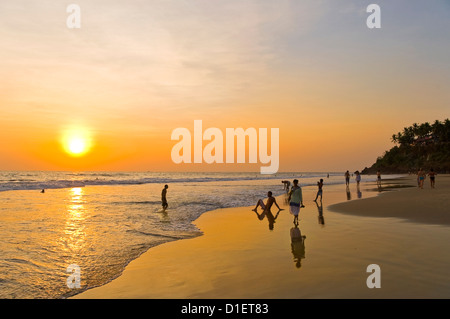 Horizontal view of people relaxing and watching the sunset on Papanasam beach in Varkala, Kerala. - Stock Photo