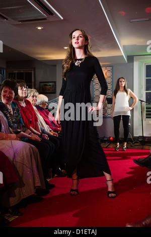 Amateur, non-professional women modeling fashion clothes on a catwalk show, charity cancer research fundraising - Stock Photo