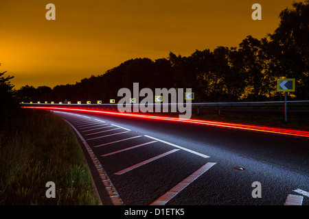 Illuminated road at sunset during the Mersey Roads 24 hour road race - Stock Photo