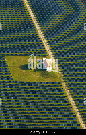 Solar panels, house and electricity pylon on a field, aerial photo - Stock Photo