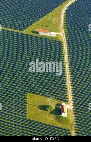 Solar panels, houses and electricity pylons on a field, aerial photo - Stock Photo