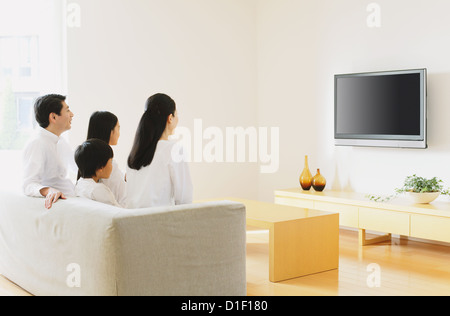 Living Room With Tv And People woman watching large flat screen tv in modern living room stock