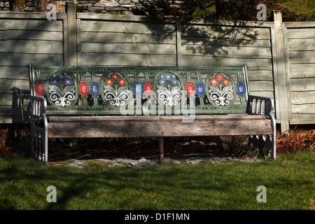 Old ornate floral painted cast iron metal and wooden garden bench seat, Cumbria, England UK - Stock Photo