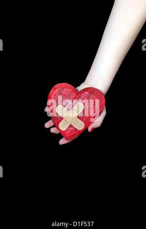 a female hand is holding a broken heart - Stock Photo