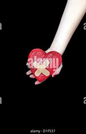 a female hand is holding a broken heart