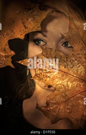 a woman is looking through leaves - Stock Photo